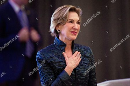 Carly Fiorina, sitting in the audience, stands as she receives acknowledgement from Vice President-elect Mike Pence acknowledges as he addresses the Heritage Foundation's 2016 President's Club Meeting in Washington
