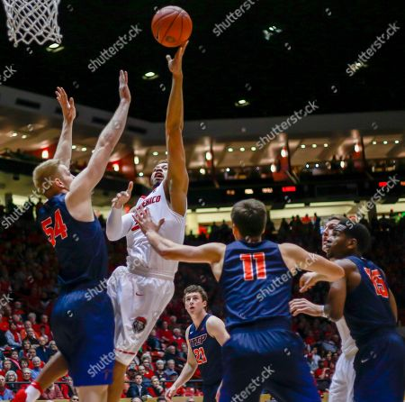 New Mexico's Xavier Adams (21), center, shoots over UTEP's Kelvin Jones (54), Jake Flaggert (11) and Dominic Artis (15) during the first half of an NCAA college basketball game in Albuquerque, N.M