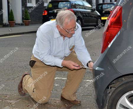 Tory Mp Sir Peter Bottomley at Work Changing the Number Plate On His Car Outside His Home in Westminster