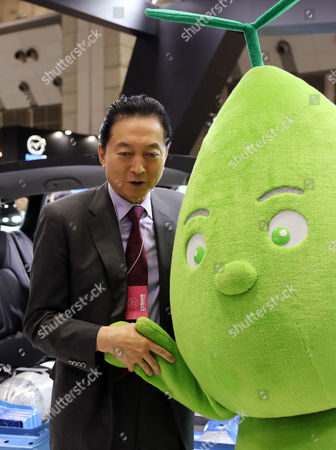 "Former Japanese Prime Minister Yukio Hatoyama smiles with automaker Honda Motor's environment character ""Leafuel"" at the ""Eco Pro 2016"" an environment exhibition in Tokyo on Thursday, December 8, 2016. Some 700 private companies, local governments, NGOs, displayed their latest technology and products in the annual three-day exhibition."