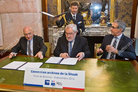 Radu Ioanid, director of the International Archival Programs Division at the United States Holocaust Memorial Museum, left, French Secretary of State for Veterans and Remembrance Jean-Marc Todeschini, center, and Jacques Fredj, Executive Director of France's Shoah Memorial attend a signing ceremony in Paris, . France's Defense Ministry signs a deal to hand over digitized versions of its archives around World War II persecution of Jews to Holocaust museums in Washington and Paris so that the public can access them
