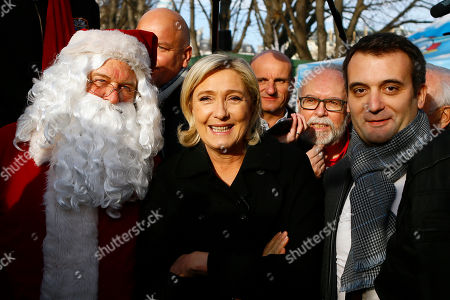 Far-right leader and candidate for next spring presidential elections Marine le Pen, center flanked with French far-right Front National vice-president Florian Philippot, right, and lawyer Wallerand de Saint Just, second right, pose with Santa Claus during a visit at Champs Elysees Christmas market in Paris