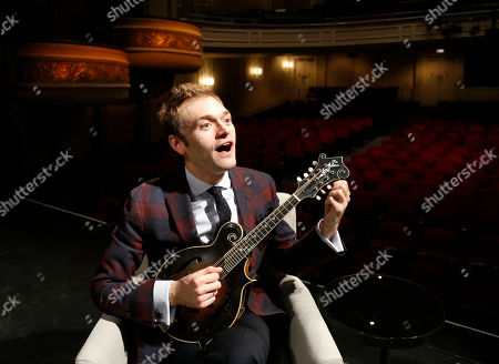 "Chris Thile plays his mandolin on stage at the Fitzgerald Theater in St. Paul, Minn. Thile says he still feels ""like a kid in a candy store"" taking over as host of the long-running public radio show ""A Prairie Home Companion."" Thile was chosen by creator Garrison Keillor to replace him on the Saturday evening show"