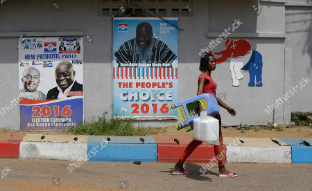 A woman walks past campaign posters of opposition presidential candidate Nana Akufo-Addo of the New Patriotic Party, in Accra Ghana, . The election is largely between two veteran politicians, incumbent President John Dramani Mahama and main opposition leader Nana Akufo-Addo