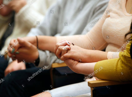 """Family members hold hands during a news conference about the surgery on conjoined twins Erika and Eva Sandoval of Antelope, Calif., at the Lucile Packard Children's Hospital, in Palo Alto, Calif. The conjoined California twins have become two separate toddlers following a marathon surgery and are recovering """"quite well,"""" officials said Thursday"""