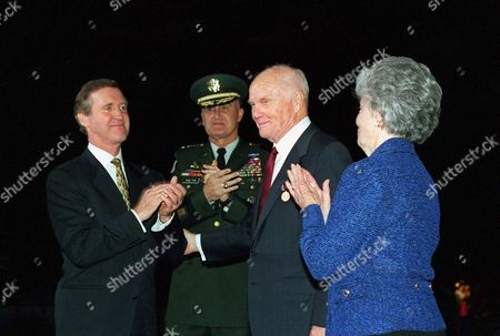 United States Secretary of Defense William S. Cohen (left) applauds U.S. Senator John H. Glenn, Jr (Democrat of Ohio) (second from right) after presenting him the Department of Defense Medal for Distinguished Public Service at an armed forces review and award ceremony at Fort Myer, Virginia,. Joining in the celebration are Chairman of the Joint Chiefs of Staff General Henry H. Shelton, (second from left) and Mrs. Annie Glenn (right). Cohen presented the medal to Glenn for his distinguished service to the nation.. Mandatory