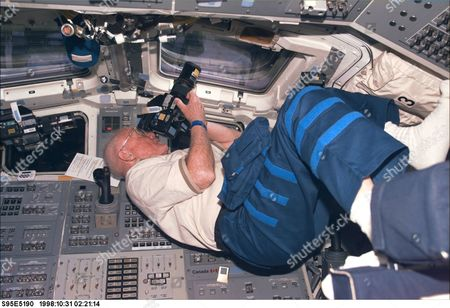 Stock Image of United States Senator John H. Glenn Jr. (Democrat of Ohio), payload specialist, focuses in on a target of opportunity as he participates in earth observations photography. The photo was taken with an electronic still camera (ESC) at 02:21:14 GMT,..