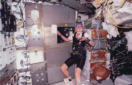 United States Senator John H. Glenn Jr. (Democrat of Ohio), equipped with sleep monitoring equipment, stands near his sleep station on the mid deck of the Earth-orbiting Space Shuttle Discovery during the mission October 29 -. The STS-95 payload specialist joined five astronauts and a Japanese payload specialist for nine days of a research mission in Earth orbit..