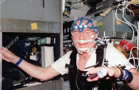 United States Senator John H. Glenn, Jr., STS-95 payload specialist, equipped with sleep monitoring equipment stands near his sleep station on the middeck of the Earth-orbiting space shuttle Discovery during the mission in Earth orbit. The payload specialist joined five astronauts and a Japanese payload specialist for nine-days of research..