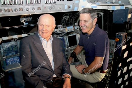 Former United States Senator John H. Glenn, Jr. (Democrat of Ohio) and Kennedy Space Center Director Bob Cabana reminisce inside the flight deck of space shuttle Discovery in the Kennedy Space Center's Orbiter Processing Facility-1 in Cape Canaveral, Florida. Glenn flew on Discovery as a mission specialist in 1998 and Cabana served as pilot for Discovery during a mission in 1990 and another in 1992..