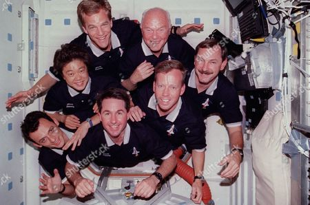 With their feet anchored in the hatchway, the seven STS-95 crew members pose for their traditional in-flight crew portrait. Astronaut Curtis L. Brown Jr., commander, appears at right center in the pyramid. Others, clockwise from there, are Steven W. Lindsey, pilot; Stephen K. Robinson, mission specialist; Pedro Duque, mission specialist representing the European Space Agency (ESA); payload specialist Chiaki Naito-Mukai, who represents Japan's National Space Development Agency (NASDA); Scott E. Parazynski, mission specialist; and United States Senator John H. Glenn Jr. (Democrat of Ohio), payload specialist..