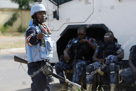 Police officers guard the entrance of Ghana electoral commission office in Accra Ghana, . Despite a relatively peaceful election, tensions are growing after the main opposition New Patriotic Party on Thursday urged incumbent President John Dramani Mahama to concede defeat after the NPP's internal polling data determined the opposition was poised to win