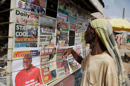 A man looks at local newspapers with on a street in Accra, Ghana, . Despite a relatively peaceful election, tensions are growing after the main opposition New Patriotic Party on Thursday urged incumbent President John Dramani Mahama to concede defeat after the NPP's internal polling data determined the opposition was poised to win