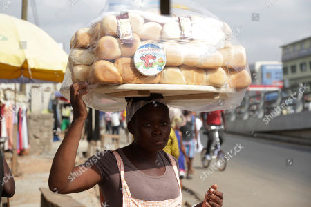 A woman sells bread on a street in Accra, Ghana, . Despite a relatively peaceful election, tensions are growing after the main opposition New Patriotic Party on Thursday urged incumbent President John Dramani Mahama to concede defeat after the NPP's internal polling data determined the opposition was poised to win