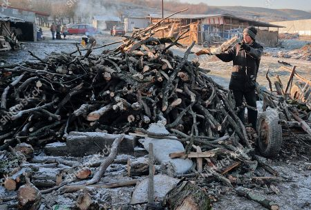 In this picture a man unloads fire wood in Dambu, Romania. Romanians will vote in parliamentary elections on Dec. 11, a year after a massive anti-corruption drive forced its last prime minister Victor Ponta from power, media moguls were imprisoned and one of the leaders of the second biggest party quit over a graft probe