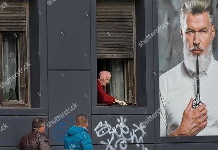 Stock Image of An elderly woman cleans a window next to an advertising poster in Bucharest, Romania, . Romanians will vote in parliamentary elections on Dec. 11, a year after a massive anti-corruption drive forced its last prime minister Victor Ponta from power, media moguls were imprisoned and one of the leaders of the second biggest party quit over a graft probe