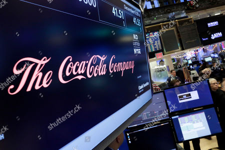 The Coca-Cola logo appears above the post where it trades on the floor of the New York Stock Exchange, . Coca-Cola said Friday that CEO Muhtar Kent will step down as CEO next year and be replaced by Chief Operating Officer James Quincey