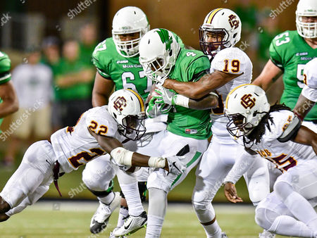 Stock Image of th, .North Texas Mean Green running back Anthony Wyche (4) .carries the ball for a first down as Bethune Cookman Wildcats safety Diquan Richardson (22) and Bethune Cookman Wildcats defensive back Jeremy Davis (19) defends during an NCAA College football game between the Bethune-Cookman Wildcats and the North Texas Mean Green at Apogee Stadium in Denton, Texas