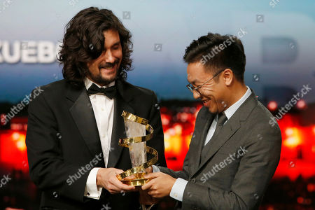 """Wang Zijian, Lisandro Alonso Producer Wang Zijian, right, poses for photographers after winning the Directing prize for the film """" Nife in the clear water """" with Jury member Argentine director Lisandro Alonso during the closing ceremony of the the 16th Marrakech International Film Festival in Marrakech, Morocco"""