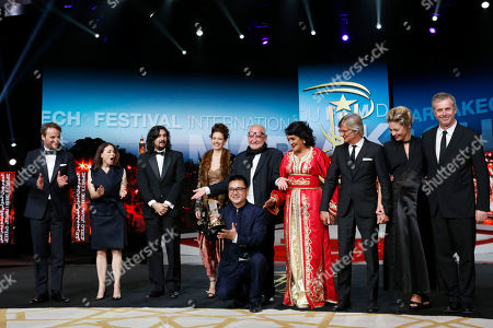 "Chinese Director Zang Qiwu poses for photographers after winning the Golden Star prize for the film ""The Donor"" with jury members Jason Clarke, Suzanne Clement, Lisandro Alonso, Kalki Koechlin, jury president Bela Tarr, Fatima Harandi ""Raouia,"" Bille August, Jasmine Trinca and Bruno Dumont during the closing ceremony of the the 16th Marrakech International Film Festival in Marrakech, Morocco"