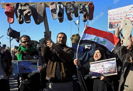 """Protesters wave shoes and slippers as they hold national flags and posters depicting Iraq's Vice President and former Prime Minister Nouri al-Maliki, with Arabic that read, """"fraudulent, leave, you have made Iraq the worst country in the world,"""" during protests against al-Maliki's visit to Basra, 340 miles (550 kilometers) southeast of Baghdad, Iraq"""