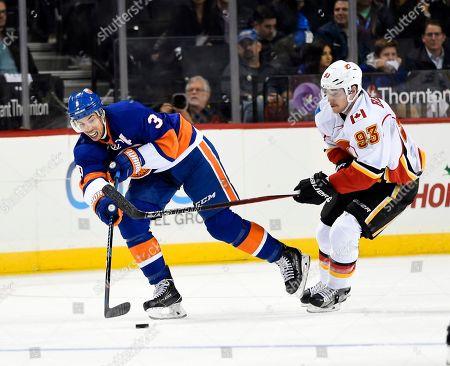 Travis Hamonic, Sam Bennett New York Islanders defenseman Travis Hamonic (3) drives the puck away from Calgary Flames center Sam Bennett (93) in the second period of an NHL hockey game in New York