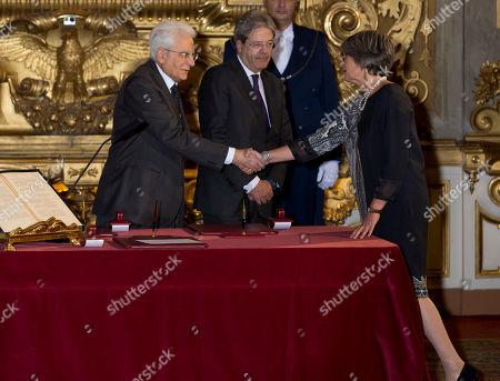 Anna Finocchiaro, right, Minister of Relations with the Parliament, shakes hands with Italian President Sergio Mattarella after taking her oath of office for Italy new's government, at Rome's Quirinale Presidential Palace, . Paolo Gentiloni, a Democrat serving as foreign minister, formed Italy's new government Monday, keeping several key ministers from the coalition of Matteo Renzi, who resigned last week