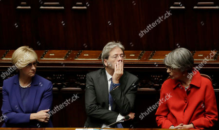 Italian Prime Minister Paolo Gentiloni sits between Anna Finocchiaro, right, and Roberta Pinotti after giving his first speech as premier at the lower house where he will later face a confidence vote, in Rome . Paolo Gentiloni, a Democrat formerly serving as foreign minister, formed Italy's new government Monday, keeping several key ministers from the coalition of Matteo Renzi, who resigned last week