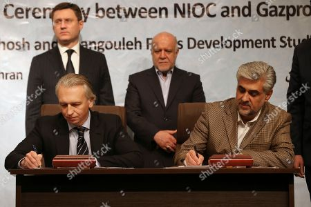 Bijan Zanganeh, Alexander Novak, Alexander Dyukov, Salbali Karimi Chairman of the management Board of Russian Gazprom Neft oil company Alexander Dyukov, seated left, and Managing Director of Iran's Central Oil Fields Company Salbali Karimi sign a memorandum of understanding as Iranian Oil Minister Bijan Zanganeh, top right, and Russian Energy Minister Alexander Novak look on in Tehran, Iran, . Iran and Russia signed memorandums of understanding on Tuesday to develop two oil fields in western Iran in a bid to boost its crude production. The two countries signed MOUs to study the Cheshmeh-Khosh and Changuleh fields of Iran