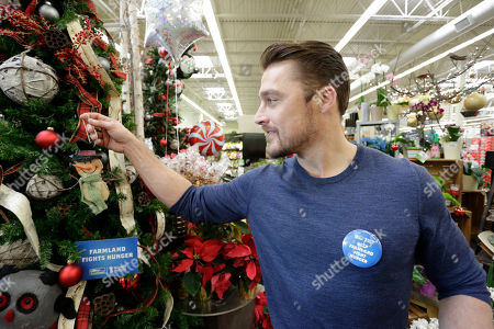 """Chris Soules, former star of the """"The Bachelor,"""" gets in the holiday spirit at a local Hy-Vee during a Farmland Fights Hunger event, in Ankeny, Iowa. For every Farmland product purchased through December 31st, twenty-five cents will be donated to No Kid Hungry, up to $100,000"""
