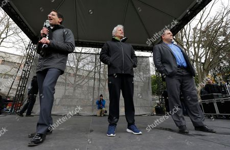 Seattle Sounders owner Adrian Hanauer, left, speaks as general manager Garth Lagerwey, right, and owners Joe Roth, center, survey the crowd during a celebration rally at the Seattle Center, in Seattle. The Sounders beat Toronto FC on Dec. 10, 2016 to win the MLS soccer championship