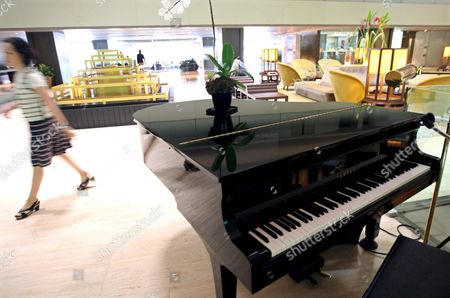 A Hotel Guest Walks Past a Piano Which Hotel Official Said Us Actor David Carradine Played Before He Was Found Dead at the Lobby of the Swissotel Nai Lert Park Hotel in Bangkok Thailand 05 June 2009 Carradine Has Been Found Dead in the Closet of His Suite On 04 June 2009