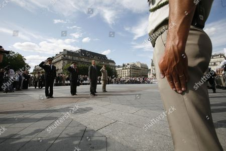 Stock Image of Paris Police Prefect Michel Gaudin (2-l) French Junior Minister For Veterans' Affairs Hubert Falco (c) Paris' Mayor Bertrand Delanoe (2-r) and French Army General Bruno Dary (r) Stand at Attention in Front of Paris City Hall While La Marseillaise is Being Played During a Ceremony Marking the 65th Anniversary of the Liberation of Paris From Nazi Occupation in Paris France 25 August 2009