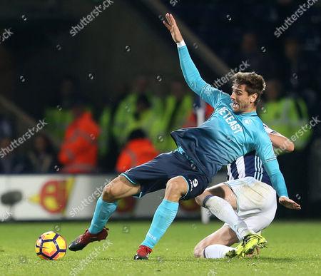 Fernando Llorente of Swansea City is bragged down by Jonas Olsson of West Bromwich Albion.