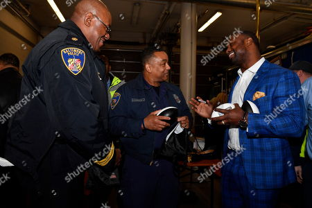 Bart Scott signs autographs with members of the Baltimore City Police & Fire Department while enjoying lunch from Chef Chad Gauss at the Built Ford Tough Toughest Tailgate at Old Town Fire House Engine #6, in Baltimore