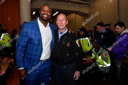 IMAGE DISTRIBUTED FOR FORD - Bart Scott poses with Captain Steven Gibson, from the Baltimore City Fire Department who is retiring today after 42 years at the Built Ford Tough Toughest Tailgate at Old Town Fire House Engine #6, in Baltimore