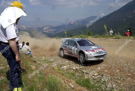 Inohori Greece : Great Britains Richard Burns and Robert Reid Drive Their Peugeot 206 Wrc at the Inohori Special Stage in Central Greece During the 49th Rally Acropolis Friday 14 June 2002 Estonian Markko Martin with Great Britains Michael Park on Ford Focus Rs Emerged As the Surprise Leader After the First Days Action in the Acropolis Rally Here on Friday Martin Finished Day One Winning Three Special Stages to Hold a Comfortable 50 7 Second Advantage Over Belgian Freddy Loix in a Hyundai Accent with Scot Colin Mcrae Breathing Down His Neck in Third