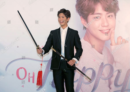 South Korean actor Park Bo-gum poses with a sword during a press conference for his Asia tour in Hong Kong