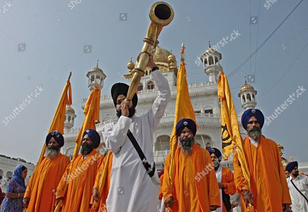 A Sikh Devotee Plays 'Ransingha' an Ancient Musical Instrument As the Panj Pyaras Or the Beloved Five Lead a Religious Procession From Inside the Golden Temple Premises in Amritsar City Punjab India On Saturday 04 November 2006 the Religious Procession Was Taken out On the Eve of the Birth Anniversary of Sri Guru Nanak Dev Ji the First Guru of the Sikhs