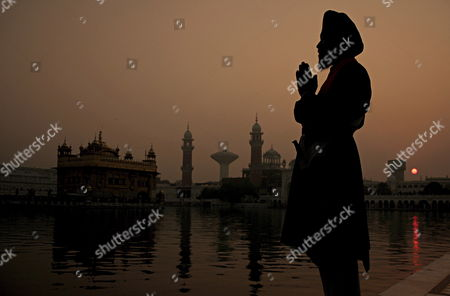 A Sikh Devotee Perorms a Ritual During the Early Morning Prayer Ceremony at the Golden Temple On the Occasion of the Birth Anniversary of Sri Guru Nanak Dev Ji the First Guru of the Sikhs in Amritsar City Punjab India On Sunday 05 November 2006