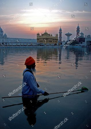 Stock Picture of A Sikh Man Performs the Early Morning 'Sewa' Or the Religious Service by Cleaning the Holy Pond of the Golden Temple On the Occasion of the Birth Anniversary of the Fifth Master Or 'Guru' of the Sikhs Guru Arjan Dev Ji in Amritsar City Punjab India On 02 May 2007 Guru Arjan Dev Ji Compiled and Installed For the First Time the Sri Guru Granth Sahib Ji the Holy Book of Sikh Religion Including Over 2 000 Hymns by Him