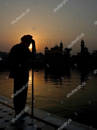 A Sikh Devotee Listens to the Early Morning Prayer at the Golden Temple Premises As the Sun Rises in the Background On the Occasion of the Birth Anniversary of the Fifth Master Or 'Guru' of the Sikhs Guru Arjan Dev Ji in Amritsar City Punjab India On 02 May 2007 Guru Arjan Dev Ji Compiled and Installed For the First Time the Sri Guru Granth Sahib Ji the Holy Book of Sikh Religion Including Over 2 000 Hymns by Him