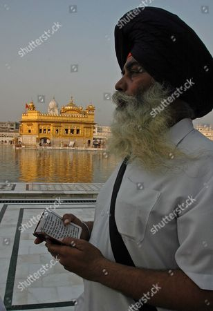 A Sikh Devotee Reads the Hymns From a Holy Book at the Golden Temple Premises On the Occasion of the Birth Anniversary of the Fifth Master Or 'Guru' of the Sikhs Guru Arjan Dev Ji in Amritsar City Punjab India On 02 May 2007 Guru Arjan Dev Ji Compiled and Installed For the First Time the Sri Guru Granth Sahib Ji the Holy Book of Sikh Religion Including Over 2 000 Hymns by Him
