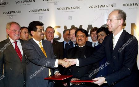 The Member of Board of Management of Volkswagen Ag Responsible For Finance Hans Dieter Potsch (r) Shakes Hands with Industry Secretary V K Jairath (2l) As Chairman of Board of Management of Skoda Auto Detlef Wittig (l) Looks On After the Signing of an Agreement in New Delhi India On Wednesday 29 November 2006 Volkswagen Ag is to Build a New Production Plant in Pune in the Indian State of Maharashtra