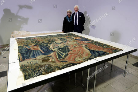 Cathy Hinz, daughter of an U.S. officer, and Robert Edsel, board member and founder of the Dallas-based Monuments Men Foundation for the Preservation of Art, pose behind a tapestry from Hitler's Eagle's Nest after the handover to the Bavarian National Museum in Munich, Germany, . The 16th century tapestry taken by Hinz' father from Adolf Hitler's retreat in the Bavarian Alps near the end of World War II is being returned to Germany