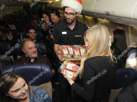 In this photo provided by Nintendo of America, Nintendo surprises passengers on a Southwest Airlines flight from Dallas Love Field to Los Angeles International Airport on Wednesday, Dec. 14. In the air, actress and YouTube celebrity iJustine gifted passengers with a New Nintendo 3DS XL system and a voucher to download Super Mario Maker for Nintendo 3DS from Nintendo eShop. From through Jan. 14, 2017, everyone can get in on the fun and enter the Say Yes to Nintendo 3DS sweepstakes for a chance to win a trip to NYC with air travel from Southwest and Nintendo prize packages
