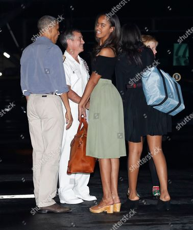 Barack Obama, Michelle Obama, Sasha Obama, Malia Obama, Harry Harris, Bruni Bradley U.S. President Barack Obama, left, with their daughters Malia, center, and Sasha, second from right, are greeted as they arrive on Air Force One, at Joint Base Pearl Harbor-Hickam, adjacent to Honolulu, Hawaii, for their annual family vacation on the island of Oahu. Greeting the first family from left are Adm. Harry Harris, commander of the U.S. Pacific Command, and his wife Bruni Bradley