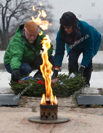 Aaron Connolly, Bethany Connolly With the Eternal Flame in front, Aaron Connolly, left, and his wife Bethany Connolly of Portland, Maine, place a wreath at the grave of President John F. Kennedy and his wife Jacqueline Bouvier Kennedy Onassis, as part of Wreaths Across America at Arlington National Cemetery, in Arlington, Va. Organizers estimate more than 245,000 wreaths were placed at graves throughout the cemetery