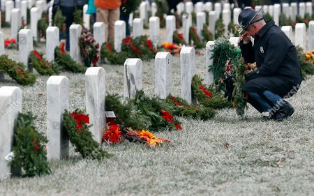 Stock Image of Maine State Police Detective Chad Lindsey pauses at a friend's grave in Section 60 as he carries a wreath to be placed at another grave, during Wreaths Across America at Arlington National Cemetery, in Arlington, Va. Organizers estimate more than 245,000 wreaths were placed at graves throughout the cemetery