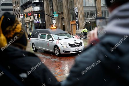 Bystanders watch as a hearse bearing the casket of John H Glenn is driven away from the Ohio Statehouse during his funeral procession, in Columbus, Ohio. The famed astronaut died Dec. 8 at age 95
